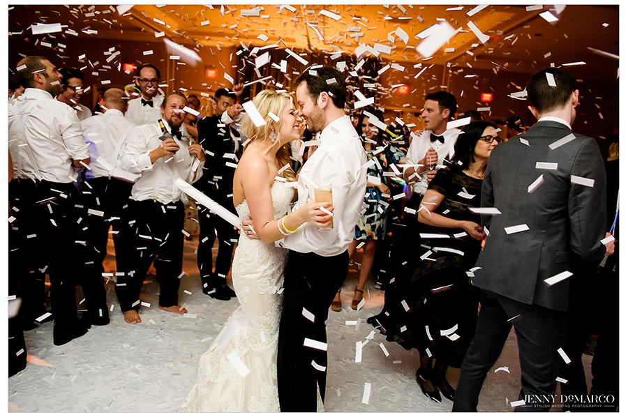 Confetti surrounding the bride and groom as they kiss at the end of the night.