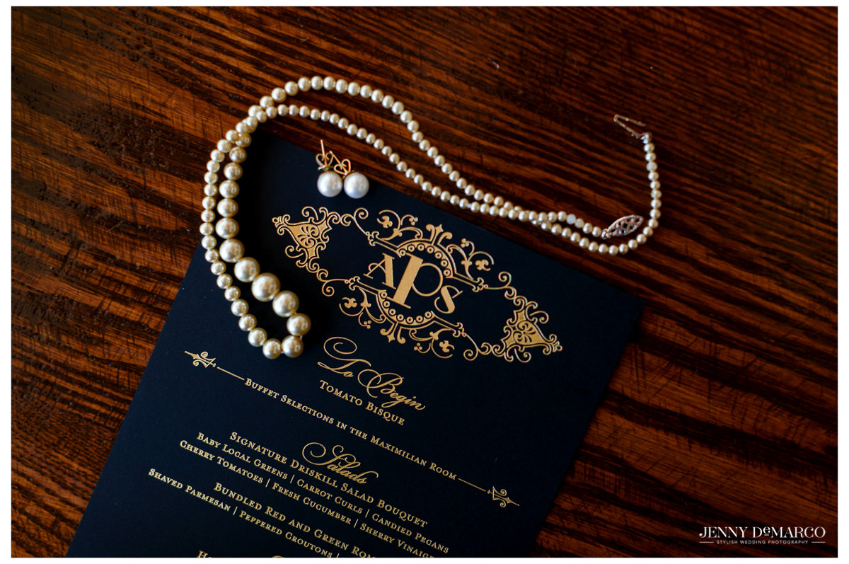 The bride's jewelry and the black and gold dinner menu.