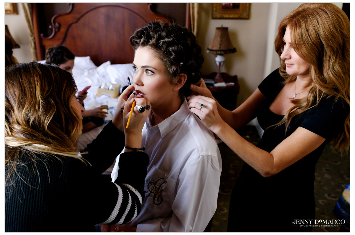 Bride getting ready with hair and makeup artists.