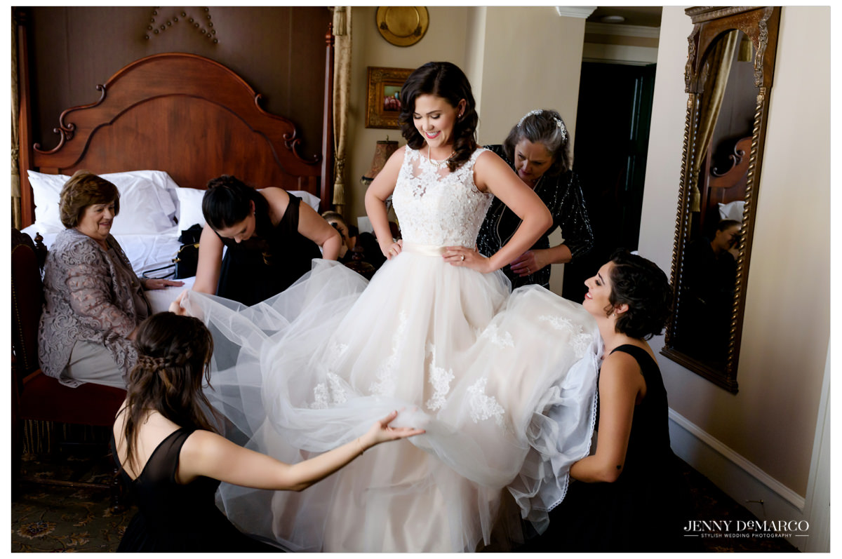 Bridesmaids helping the bride get in her dress.