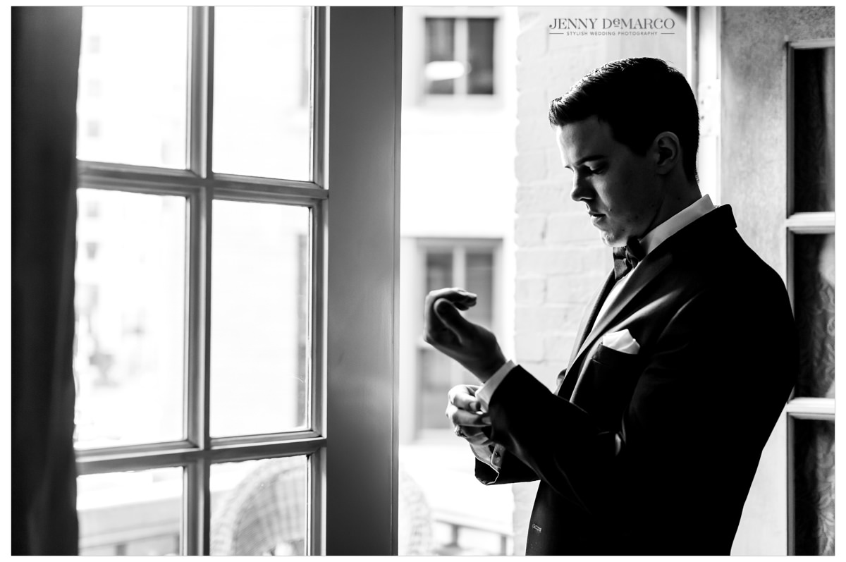 The groom putting the final touches on his outfit before the ceremony.