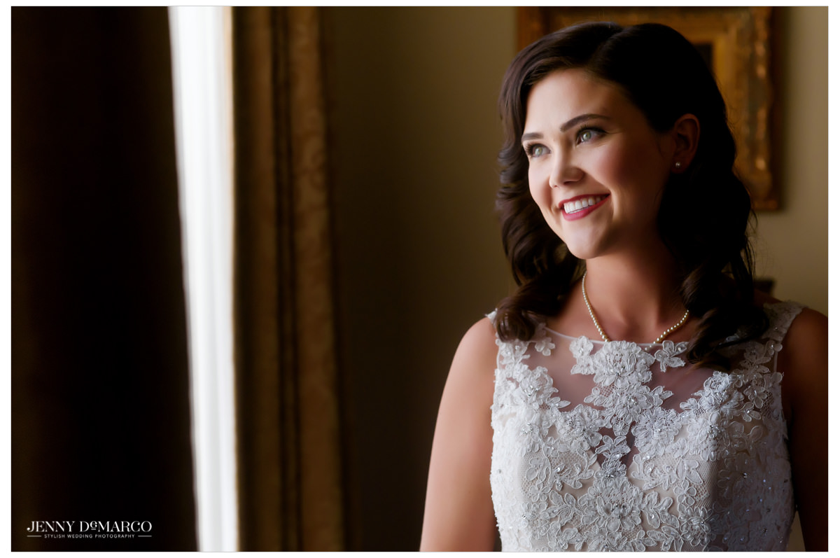 Bride looking beautiful by the window in her hotel room just before the ceremony.