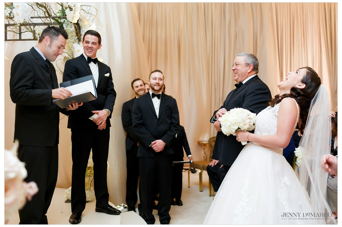 The wedding party laughing during the ceremony as the father gives the daughter away.