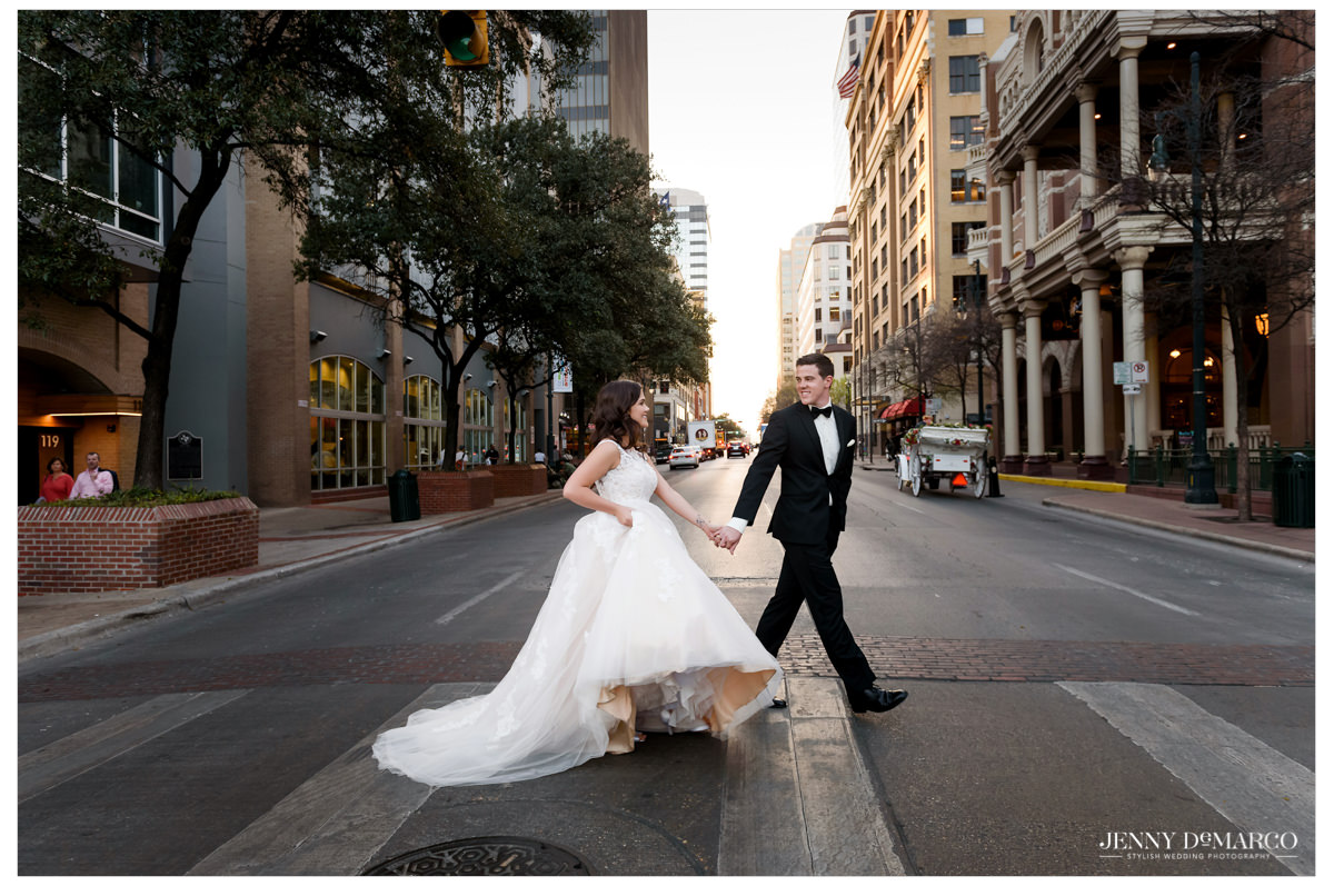 Just married bride and groom walk across 6th street in Austin, Texas.