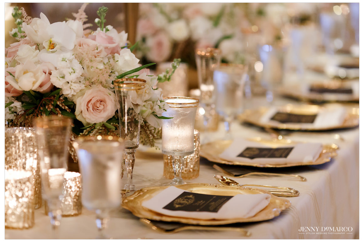 Details of the reception: gold and black dining room with pastel flower centerpieces from David Kurio Designs