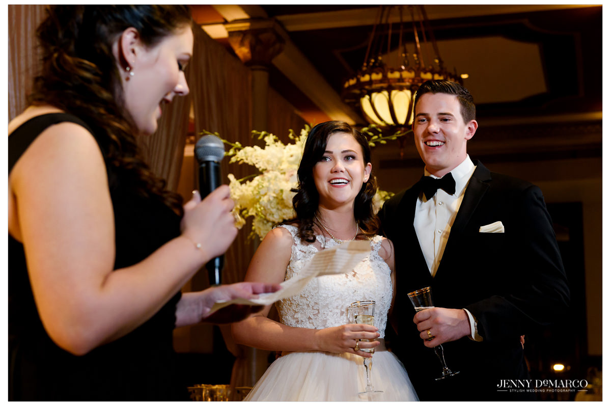The bride and groom laugh during the toast given by the Maid of Honor.