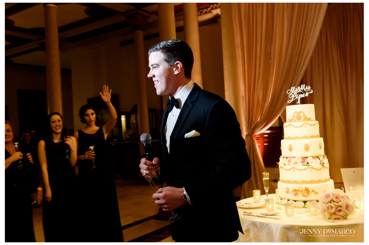 The groom gives a toast near the beautiful wedding cake.
