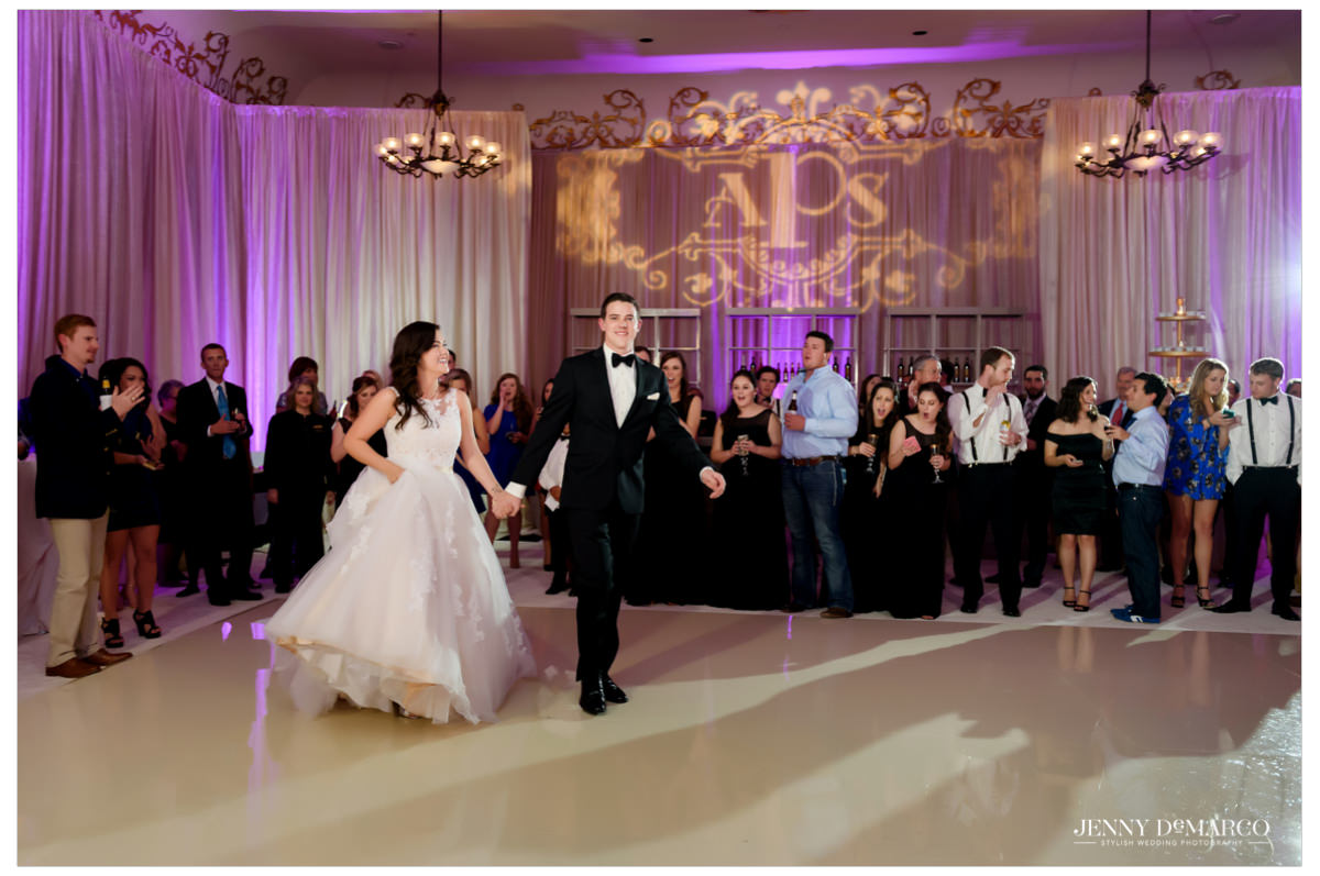 The bride and the groom walk out onto the dance floor for their first dance.