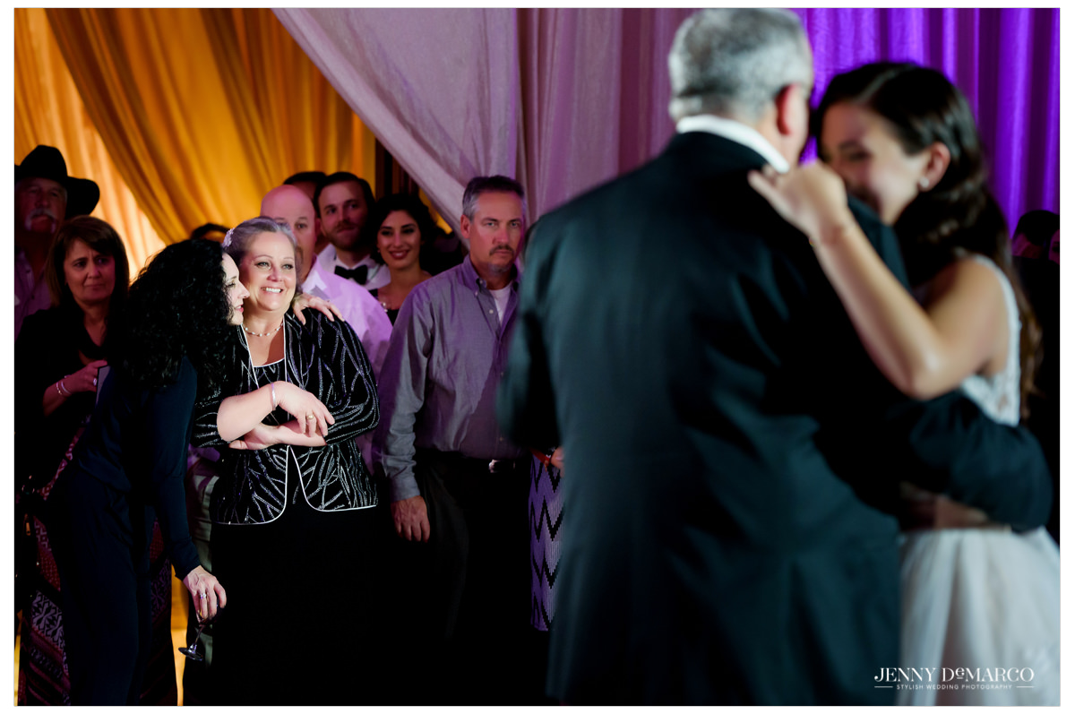 The mother of the bride watches the father daughter dance with love.