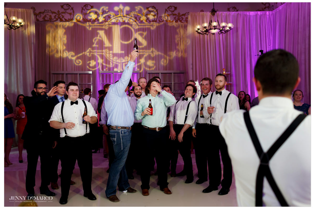 The male guests wait patiently as the garter toss is about to begin