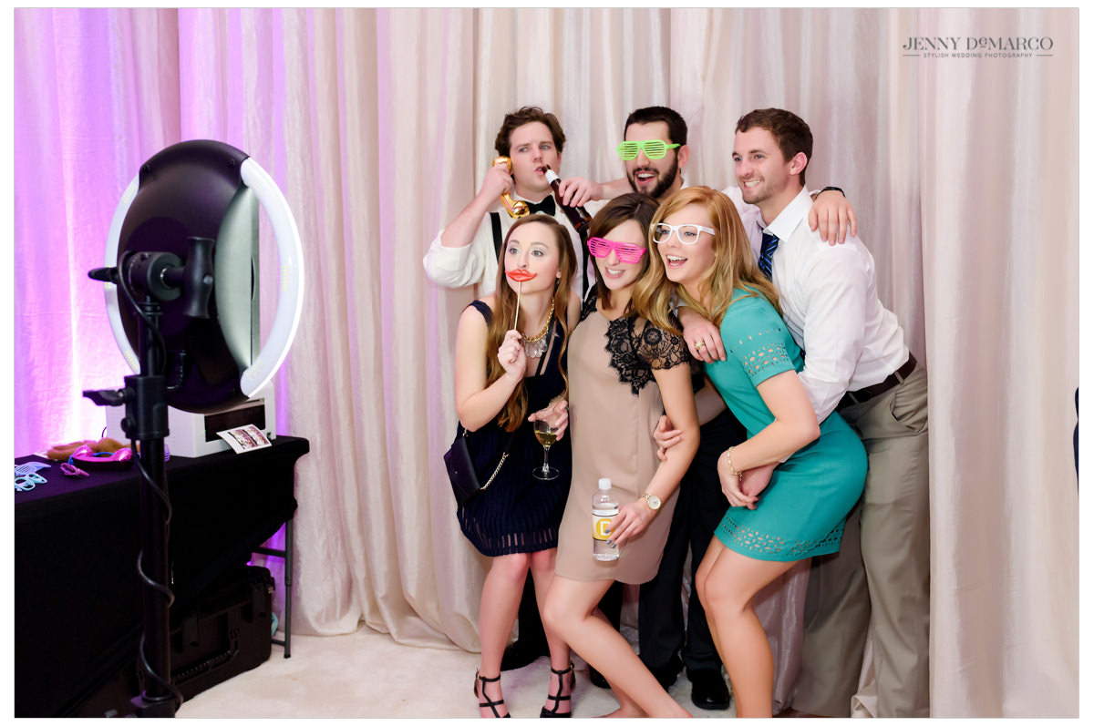 Wedding guests pose with props and fun glasses.