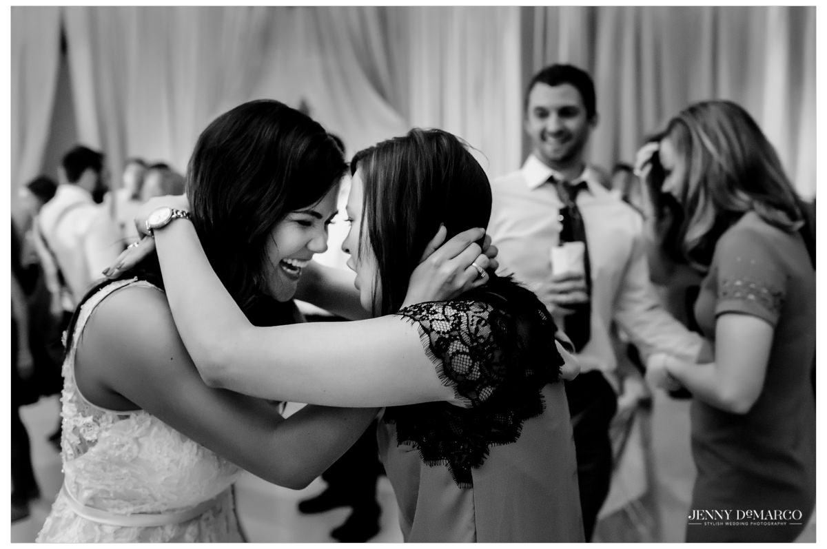 The bride and her friend sharing an intimate moment at the reception.