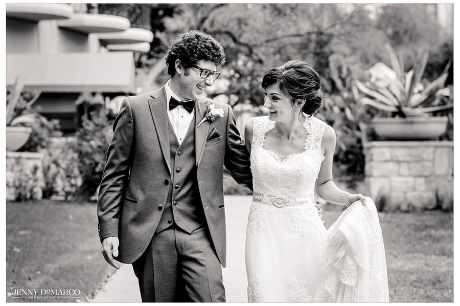 Black and white portrait of bride and groom walking together through Four Season's Hotel courtyard.