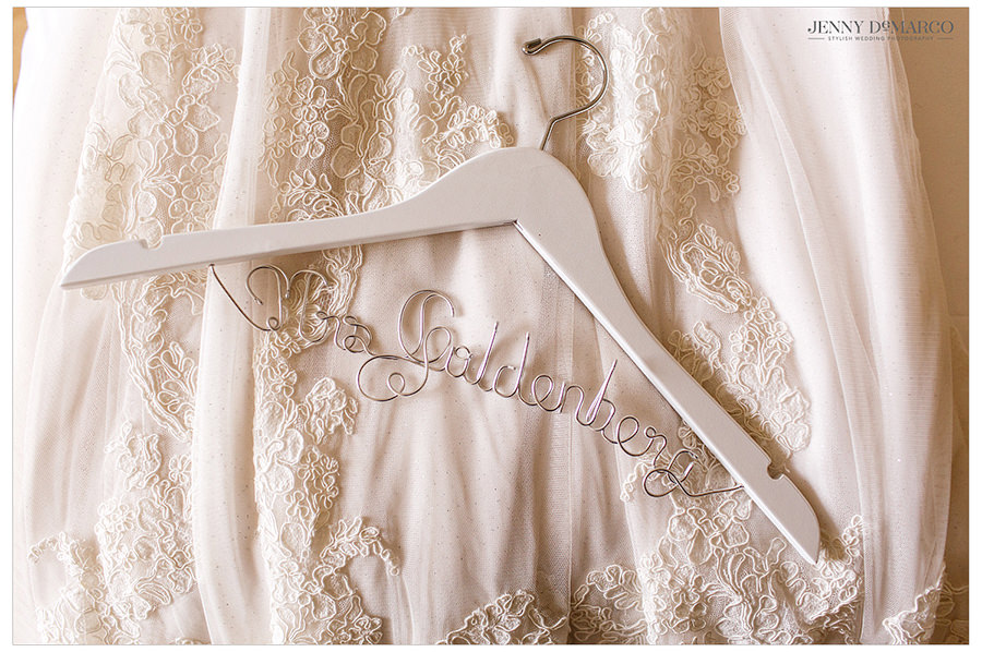 A close-up shot of the details of the wedding gown and clothing hanger with the brides new last name.