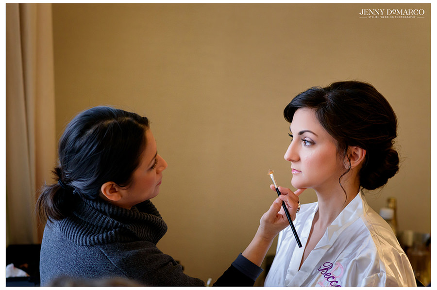 The makeup artist applies eyeshadow to the bride before the wedding.