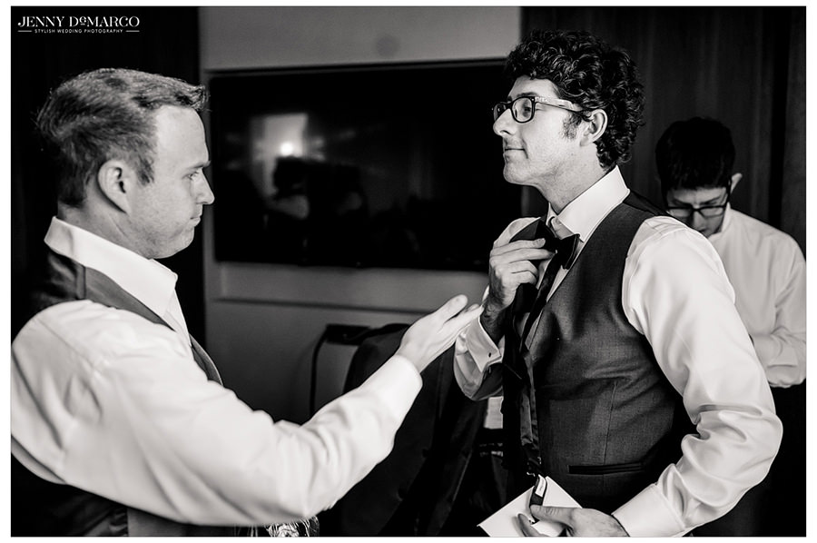 One of the groomsmen helps the groom adjust his bowtie.