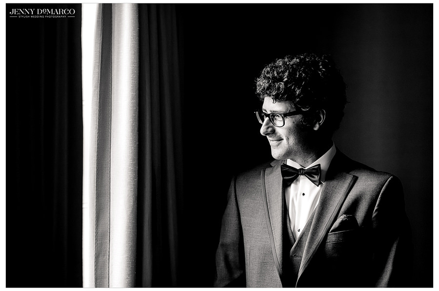 A black and white portrait of the groom in his tuxedo.