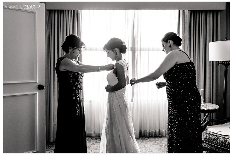 A black and white photo of the mother of the bride and her bridesmaid helping the bride with the finishing touches on her wedding dress.
