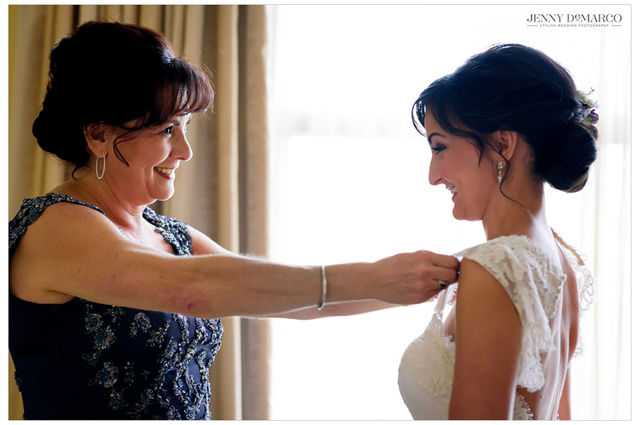 The mother of the bride shares a moment with the bride as she completes her wedding look.