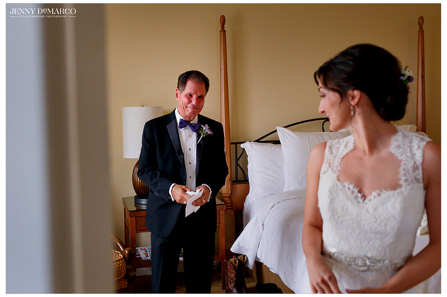 The father of the bride looks at his daughter with tears in his eyes and is overwhelmed with joy for her wedding day.