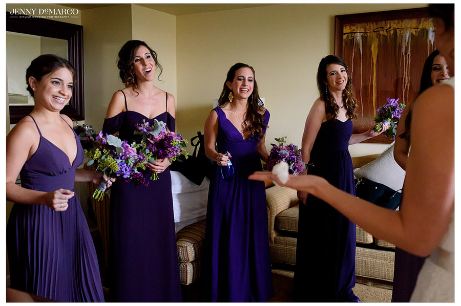 The bridesmaids. holding flowers and in purple dresses, are in awe at the beauty of the bride in her wedding dress.