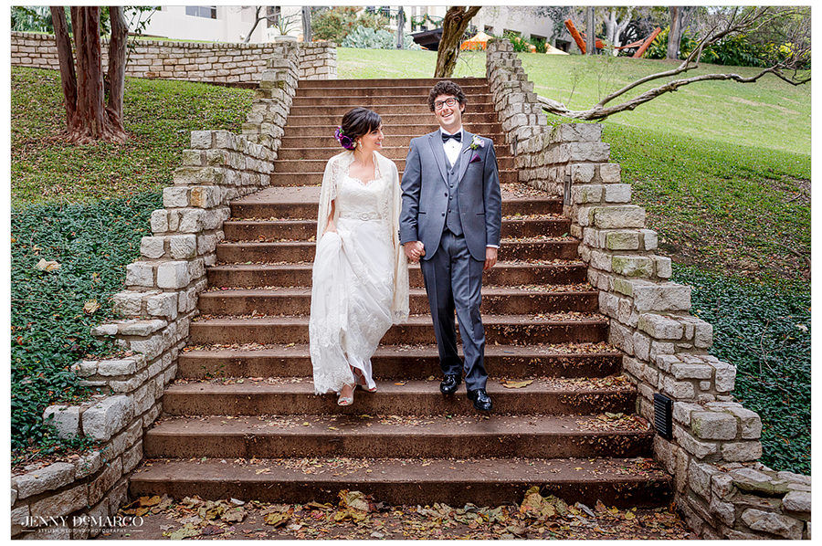 The bride and groom walk with each other down steps to the ceremony site.