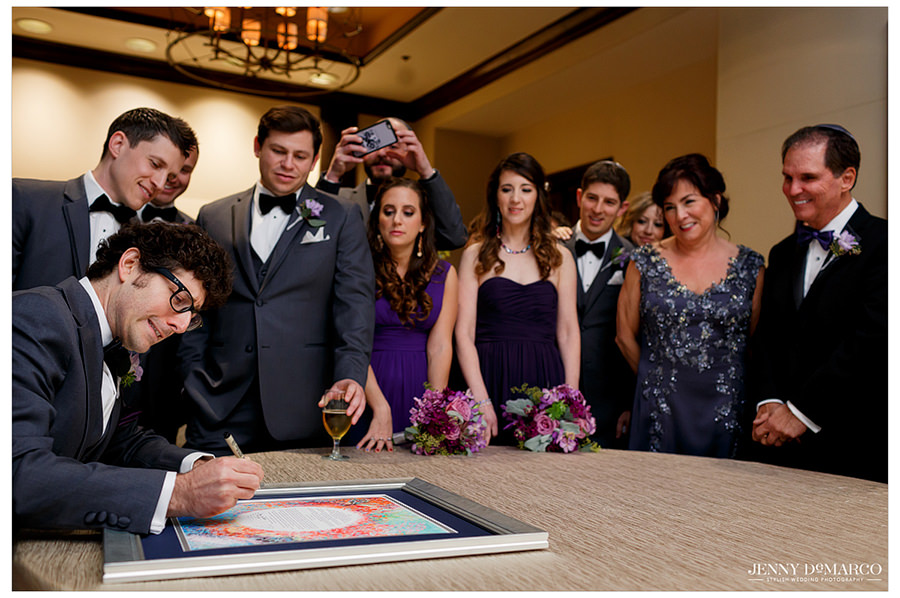 The groom signs the Katuba while family and friends gather around to watch the Jewish tradition.