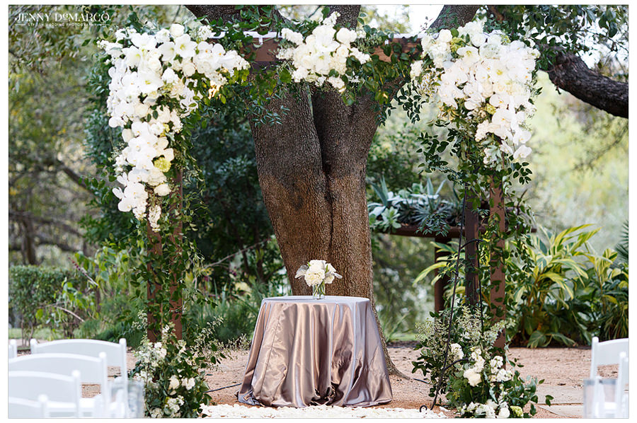 A close up of the beautiful white flower structure which is over the front of the ceremony location traced with white flowers.