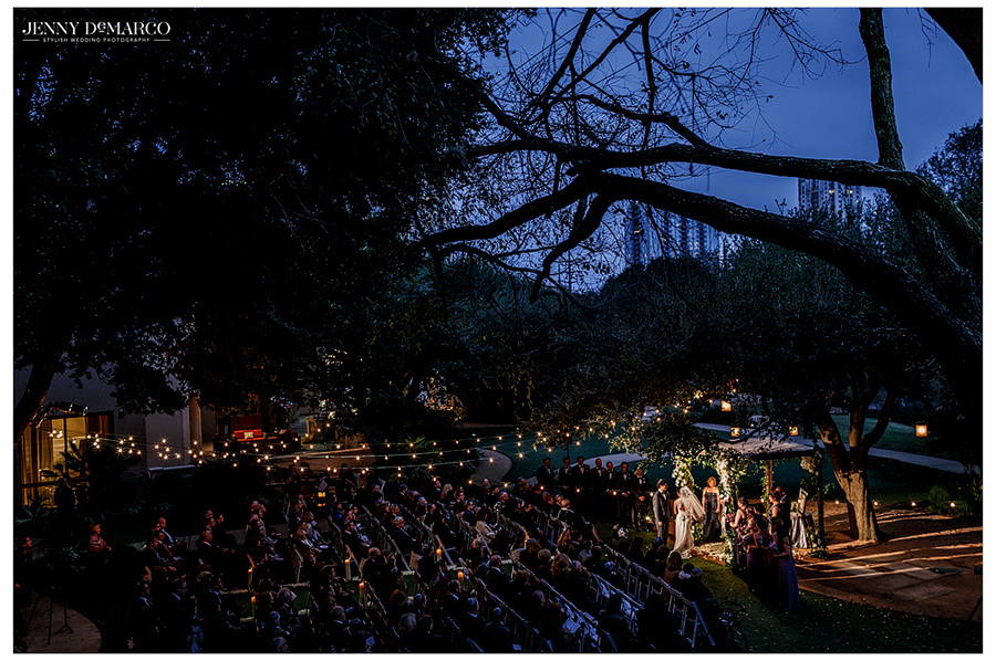 A landscape overview of the ceremony location at The Four Season's detailed with white lights and the Austin skyline in the background.