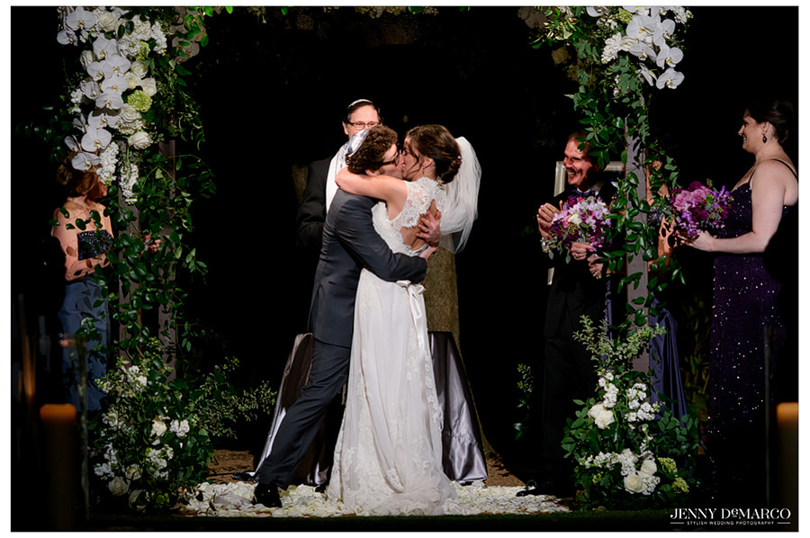 The bride and groom kiss during the nighttime ceremony.