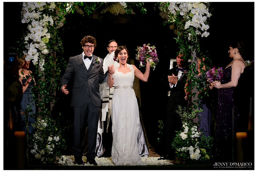 The newlyweds hold hands and cheer as they proceed down the aisle the exit the ceremony.