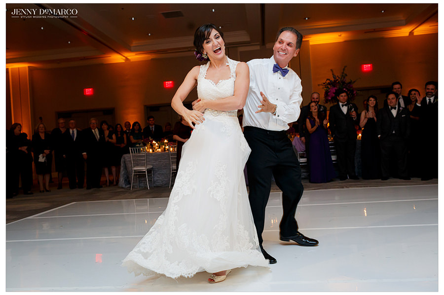 The bride's father spins her as they dance together on the ballroom floor.