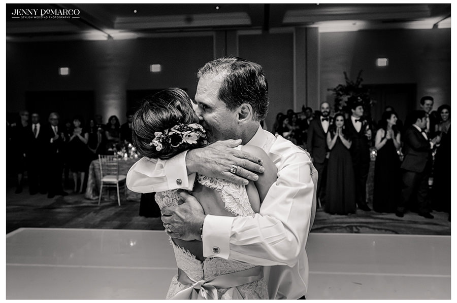 The father of the bride gives his daughter a tight hug and a kiss after their father daughter dance.