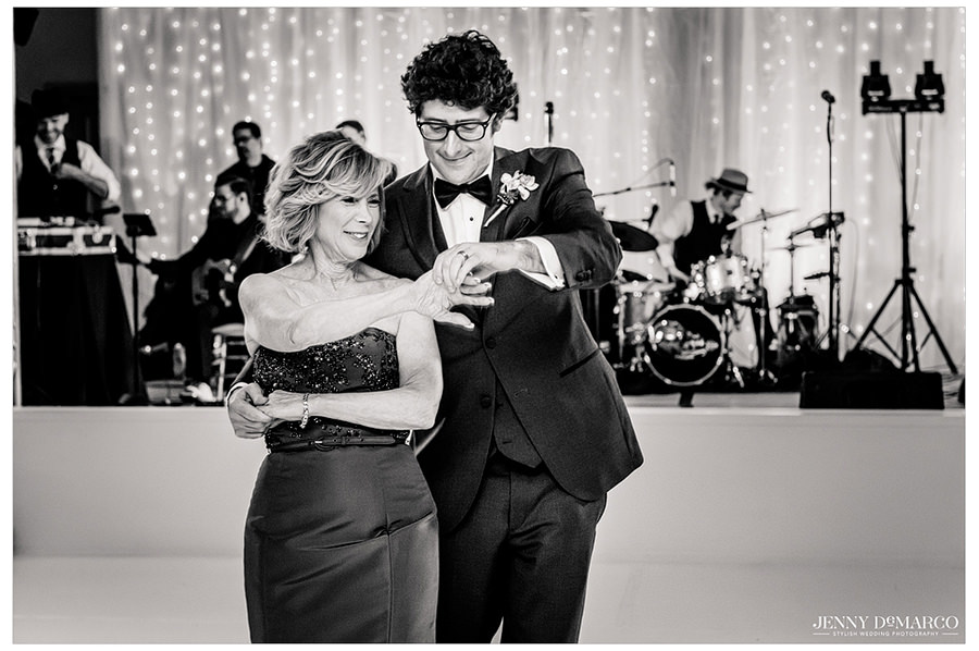 A black and white shot of the groom and his mother sharing a dance in front of the band.