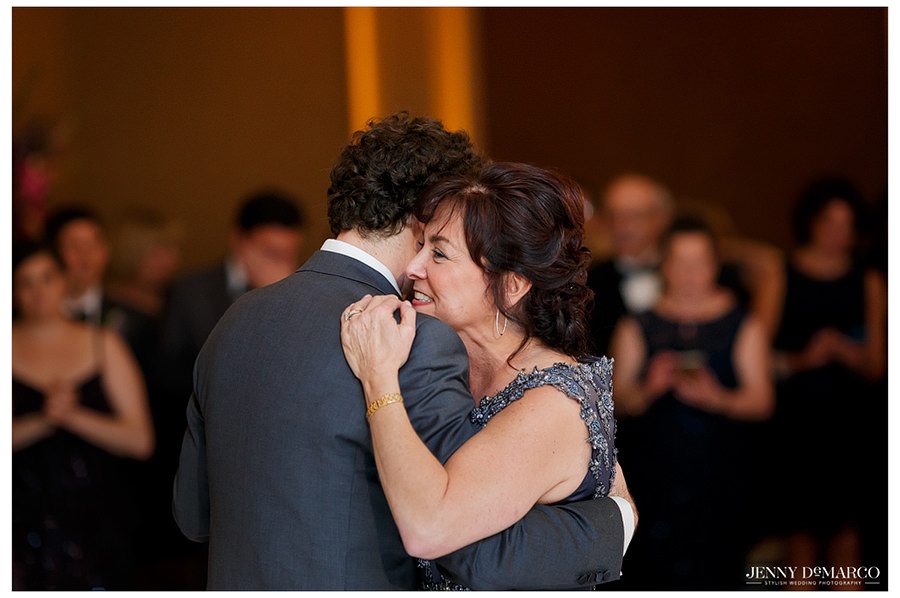 The groom and his mother hug and dancing closely as family and friends gather to watch.