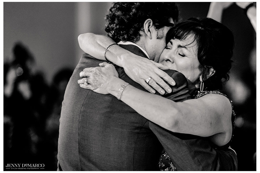 A close up black and white shot of the mother and the groom hugging and sharing a moment.