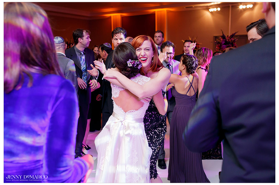 The bride hugs a guest and shares a moment on the dance floor in the ballroom of the Four Seasons.