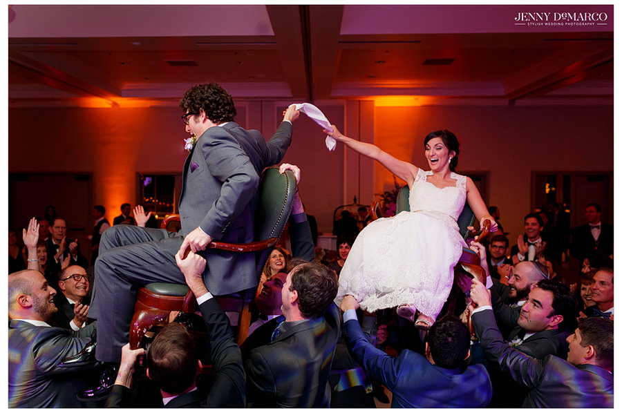 The bride and groom are raised up on their chairs by their guests for the hora.
