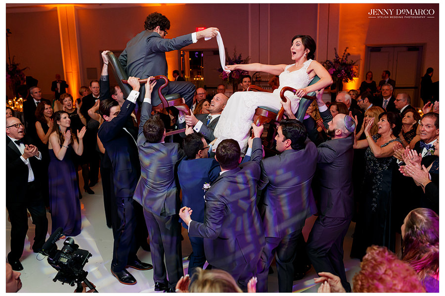 Guests hold the bride and groom up on their chairs for the hora.