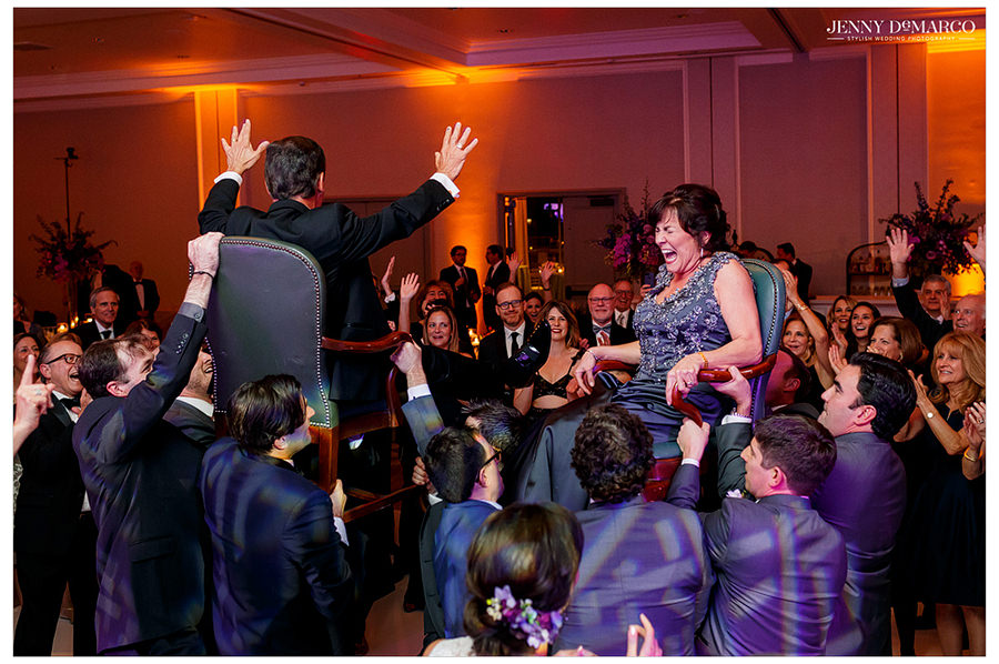The mother and the father are lifted up in their chairs by guests for the hora.