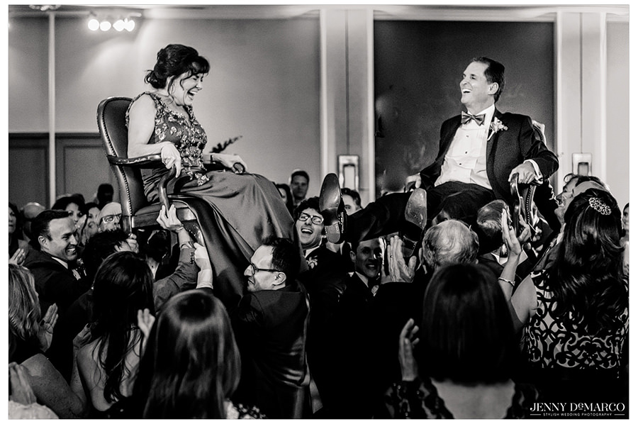 A black and white shot of the mother and father of the bride laughing during the tradition of the hora.