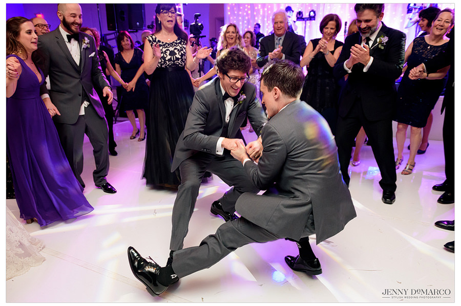 The groom and one of this groomsmen hold hands and dance together while guests gather to watch and laugh.