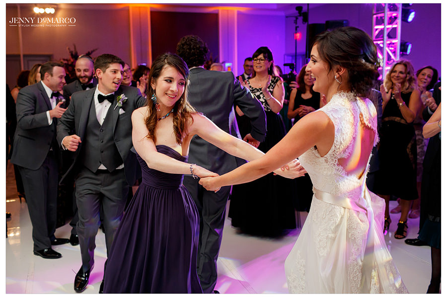 The bride and her bridesmaid hold hands and dance while guests clap along to the music.