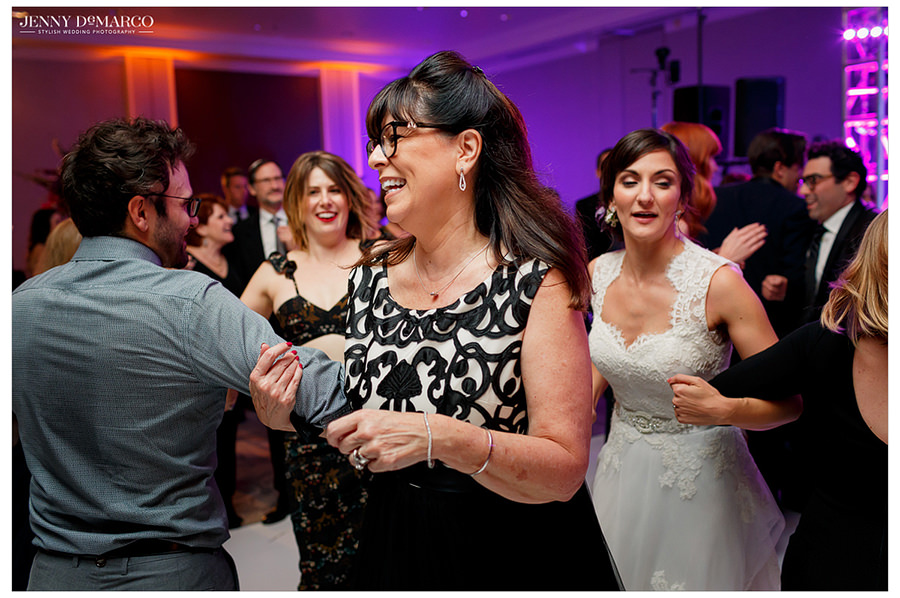 A guest smiles as she dances at the reception with other guests.