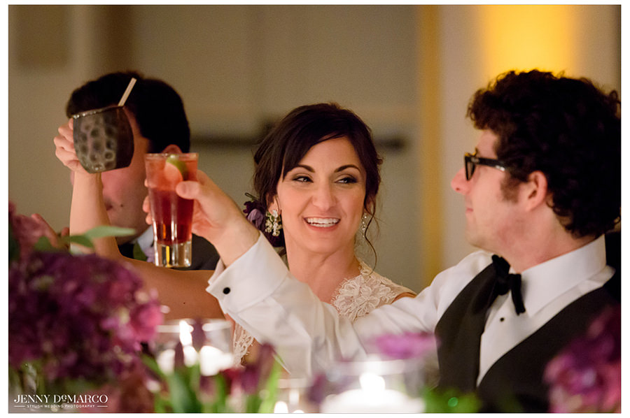 The bride and groom raise their glasses for a toast.