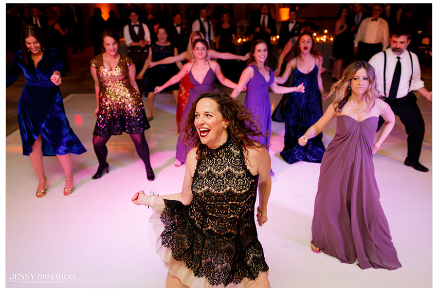 The bridesmaids and guests gather to perform a choreographed dance for the bride.