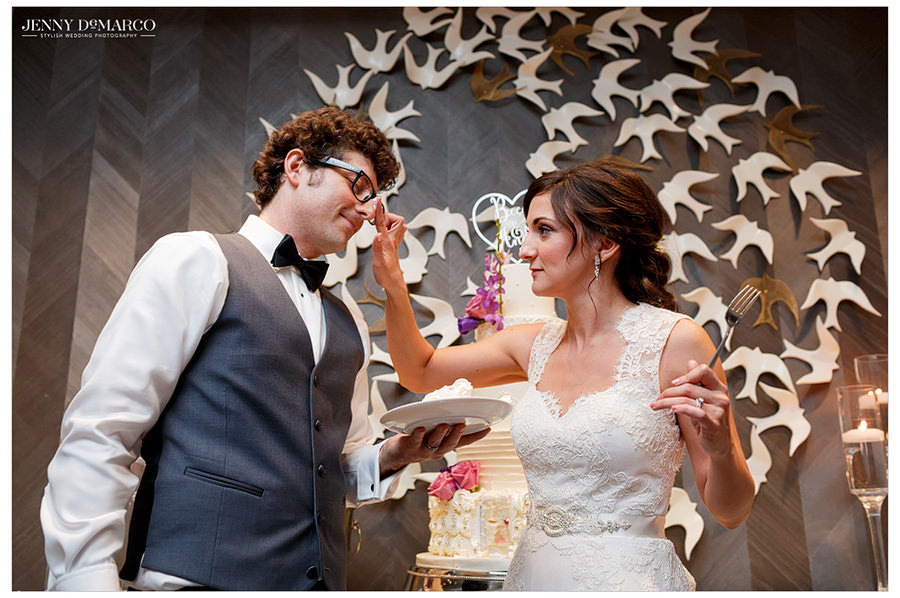 The bride playfully smudges icing from the cake on the grooms nose as he laughs after they cut the wedding cake.