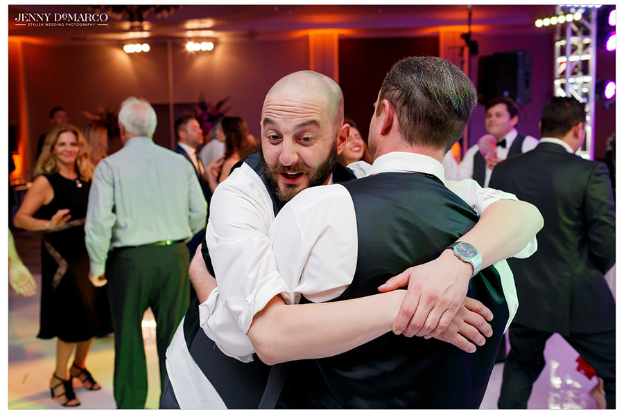 Groomsmen hug and dance with other guests at the reception.