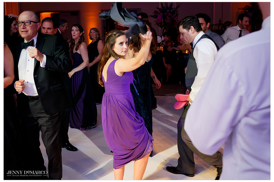 A guests waves around a groomsmen's jacket as she dances.