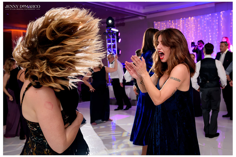 Guests wave their hair and clap as their dance to the music at the reception.